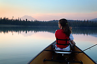 Girl paddling canoe on Hosmer Lake at dusk, Mountain Bachelor in background, Cascade Lakes, Oregon, USA