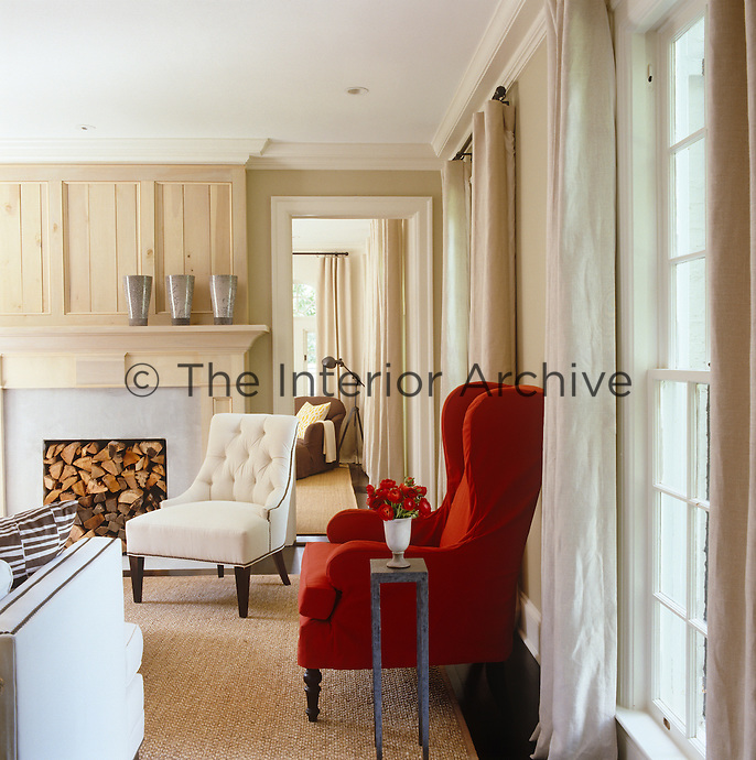 White tufted chairs, creamy linen curtains, and an abaca carpet present a neutral backdrop for the red slipcovered wing chairs in this pared-down living room