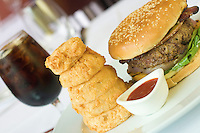 Upscale Kobe Beef hamburger with a stack of onion rings,  and a soda in the background.