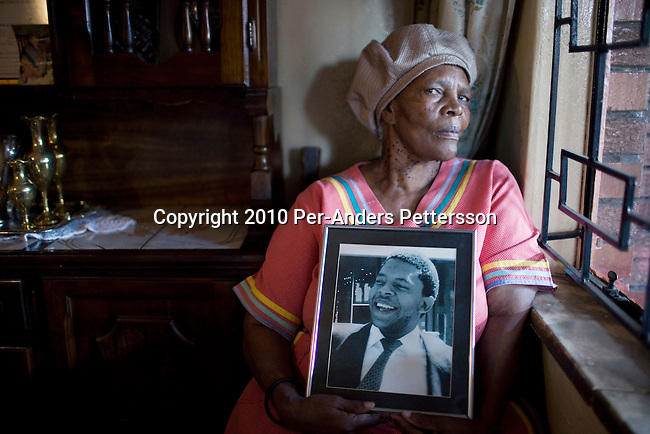 SOWETO, SOUTH AFRICA - APRIL 14:Mamosadi Catherine Mlangeni, a victim of Apartheid, holds a portrait of her killed sonon April 14 2010, in Soweto, South Africa. Khulumani is involved among other things in a lawsuit  against Daimler AG, with complaints brought forward by victims of Apartheid. Theplaintiffsargue that Daimler soldvehicles to the old South African government, and they were used by the police and security forces to keep up the Apartheid regime. (Photo by Per-AndersPettersson/Getty Images)