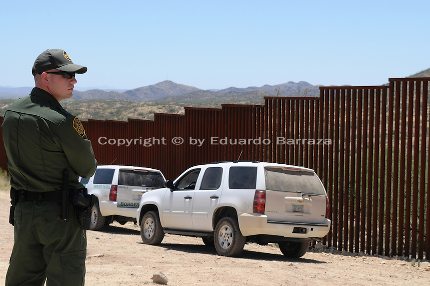 Sasabe, Arizona – U.S. Customs Border Protection (CBP) Public Affairs Officer J. Copeland stands next to the U.S.-Mexico border fence on a dirt road near Sasabe, Arizona. He transported journalists to a remote area where they walked through a 1.3 miles trail during a two-day event organized by the Tucson Sector Border Patrol. The event brought national and international journalists to the Arizona desert to become acquainted with the dynamics of this area. This area is located near the Sasabe Port of Entry, a border-crossing station located in southern Arizona, and about 70 miles from the City of Tucson. Sasabe is one of the most isolated ports along the 2,000-mile U.S.-Mexico border, and it connects the towns of Sasabe, Arizona and El Sasabe, Sonora (Mexico). The border-crossing station is located in one of the busiest human and drug smuggling corridors of the U.S.-Mexico border. Photo by Eduardo Barraza © 2012