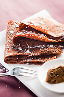 Chocolate crêpes dusted with icing sugar and served with coffee ice cream