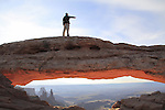 Man pointing from Mesa Arch, Island in the Sky area, Canyonlands National Park, Utah, USA. .  John offers private photo tours in  Canyonlands National Park and throughout Utah and Colorado. Year-round.