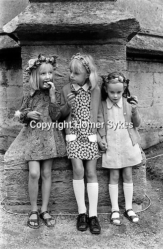 "Painswick Clypping Gloucestershire Uk Girls eating ""Clypping Buns""."