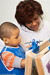 Education Preschool 2-3 year olds female teacher with boy at easel looking at and talking about his work