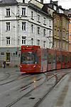 Red tram on a wet day against a background of shops and apartments. Innsbruck, Tyrol, Austria.