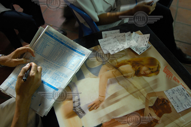 A punter examining the horse racing form before placing a bet in a cafe at Ho Chi Minh race track (Saigon Racing Club).
