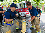WATERBURY,  CT-071919JS11--  Waterbury firefighters Joel Rodriguez, left, and Erik Bellagamba, with Engine 7 on Walnut Street, open a fire hydrant in Berkeley Heights to allow residents to cool themselves on an oppressively hot Saturday afternoon during a block party. <br /> Jim Shannon Republican American