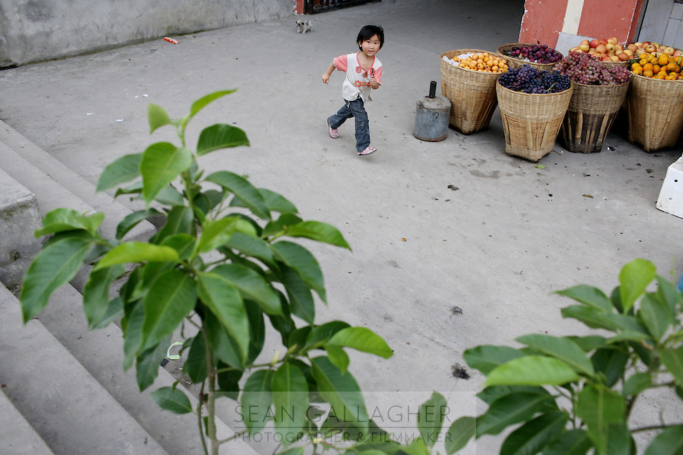 A small child runs near to a shop selling fruit, in a small town in western Sichuan  Province, China.