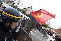 un manifestante sventola la bandiera del sindacato di fronte allo schieramento di polizia