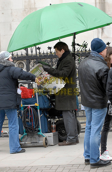 "JAMIE BAMBER.Filming on the set of ""Law & Order: UK"" (Season 1, Episode 1), Royal Courts of Justice, London, England..February 15th, 2009.full length brown coat profile reading paper umbrella sport .CAP/IA.©Ian Allis/Capital Pictures."