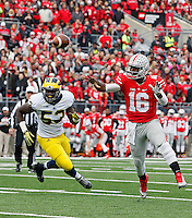 Ohio State Buckeyes quarterback J.T. Barrett (16) avoids the rush by Michigan Wolverines defensive end Mario Ojemudia (53) and throws a touchdown pass in the 1st quarter of their game at Ohio Stadium in Columbus, Ohio on November 29, 2014.  (Dispatch photo by Kyle Robertson)