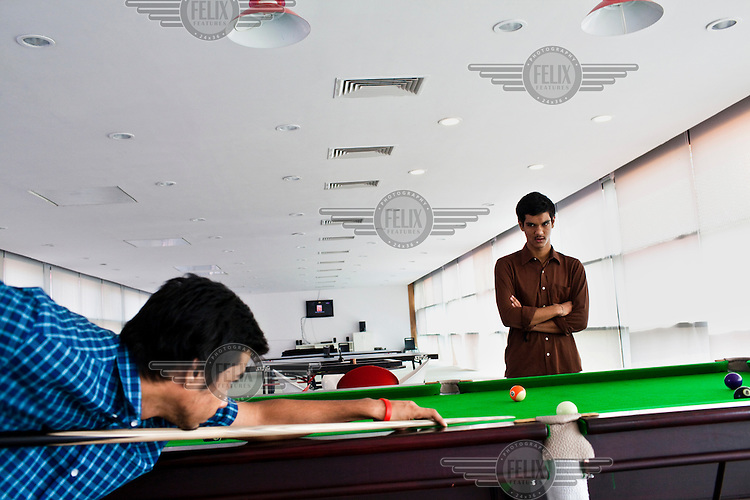 Gaureesh Dubey (right) looks on while Devasheesh Dubey strikes the ball on the pool table in the recreation hall of the Jindal Global University in Sonepat.