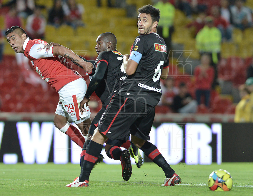 BOGOTÁ -COLOMBIA, 29-09-2013. Silvio Gonzalez (I) de Santa Fe disputa el balón con Andres Mosquera (C) del Medellín durante partido  por la fecha 12 de la Liga Postobon II 2013 disputado en el estadio el Campín de la ciudad de Bogotá./ Santa Fe player Juan D. Roa (L) fights for the ball with Medellin player Jhon Hernandez (C) during match of the 12th date for the Postobon League II 2013 played at El Campin stadium in Bogotá city. Photo: VizzorImage/Gabriel Aponte/STR
