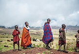 TANZANIA, Maasai Kids walking in Ngorongoro Conservation Area, Animals in the background
