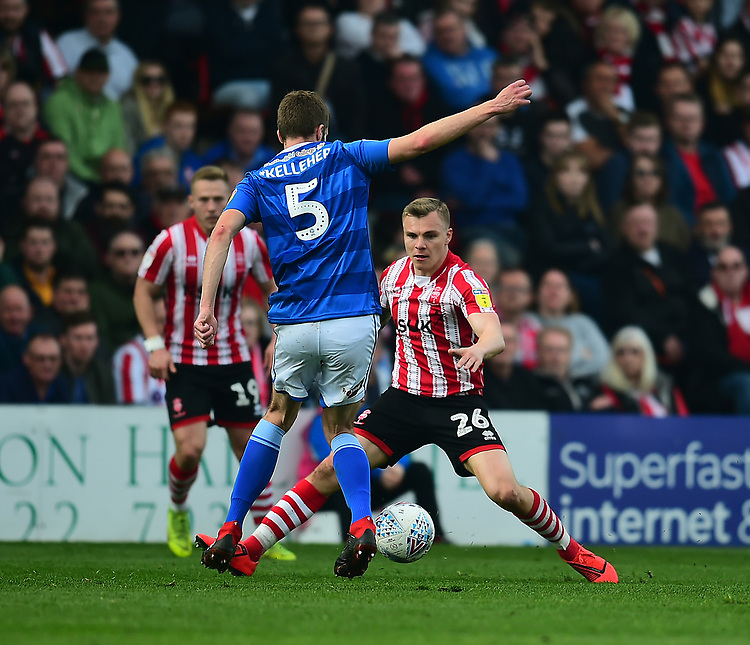 Lincoln City's Harry Anderson vies for possession with  Macclesfield Town's Fiacre Kelleher<br /> <br /> Photographer Andrew Vaughan/CameraSport<br /> <br /> The EFL Sky Bet League Two - Lincoln City v Macclesfield Town - Saturday 30th March 2019 - Sincil Bank - Lincoln<br /> <br /> World Copyright © 2019 CameraSport. All rights reserved. 43 Linden Ave. Countesthorpe. Leicester. England. LE8 5PG - Tel: +44 (0) 116 277 4147 - admin@camerasport.com - www.camerasport.com