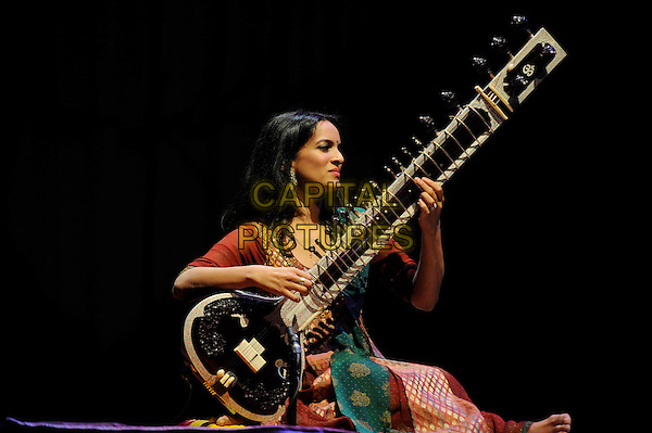 Anoushka Shankar.performing in concert, Queen Elizabeth Hall, Waterloo, London, England, UK, 13th April 2013..music live on stage performing gig half full length sitting indian dress sari costume orange red gold embroidered patterned green silk  playing sitar instrument traditional Indian classical bare foot feet .CAP/MAR.© Martin Harris/Capital Pictures.