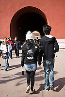 Young Chinese couple in modern western clothing at the Forbidden City entrance, Beijing, China