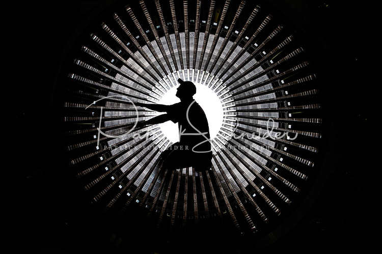 An employee of Siemens Charlotte Turbine-Generator Center inspects the inside of a stator core, which is the stationary part of a generator's rotor system. Siemens state-of-the-art generator manufacturing operations include new-unit generator manufacturing as well as service repairs for steam turbines and generators. The Charlotte NC manufacturing facility was founded in 1967 by Westinghouse Electric Corporation to manufacture nuclear low pressure turbines. Siemens Charlotte plant is the primary service center for generator and steam turbine equipment in the Americas, and the lead plant for manufacturing new electrical generators. Internationally, Siemens AG is Europe's largest engineering conglomerate.