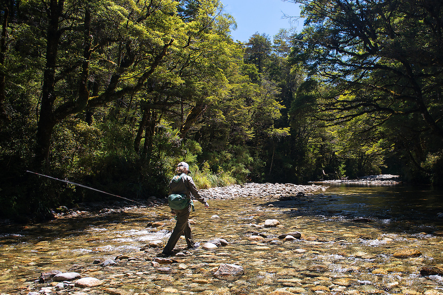 An angler hikes up a riverbed in search of brown trout on New Zealand's South Island.