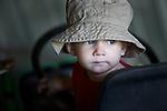 A young boy wearing a hat sits on farm equipment in the Saskatchewan prairies in Canada.
