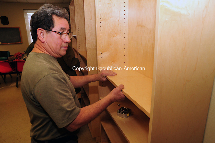 PLYMOUTH CT, 06 FEB 13-020613AJ01- Hiram Morales, owner of The Wood Mill in Plymouth, installs bookshelves in the senior center in Town Hall on Tuesday. The business donated new wooded bookshelves that will be used by senior citizens for a lending library.   Alec Johnson/ Republican-American