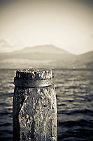 Pole on the Inveraray Ferry Terminal, facing Loch Fyne, Scotland. Mountains across Loch Shira as background..Inveraray (Inbihir Aora in Gaelic), is a picturesque little town on the western shore of Loch Fyne and is made popular by the Inveraray Castle and the Historic Jail.
