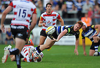Rory Jennings of Bath Rugby offloads the ball after being tackled to ground. West Country Challenge Cup match, between Gloucester Rugby and Bath Rugby on September 13, 2015 at the Memorial Stadium in Bristol, England. Photo by: Patrick Khachfe / Onside Images