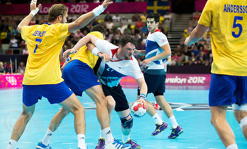 31 JUL 2012 - LONDON, GBR - Chris McDermott (GBR) of Great Britain (centre) looks for a way through Sweden's defence during the men's London 2012 Olympic Games Preliminary round match at The Copper Box in the Olympic Park, in Stratford, London, Great Britain (PHOTO (C) 2012 NIGEL FARROW)