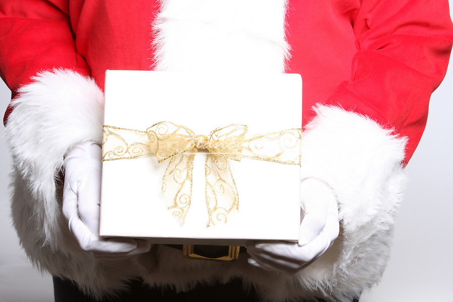 Santa Claus holding a white gift with a gold bow