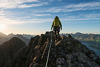 Female mountaineer on the summit of Solbjørntind mountain peak, Moskenesøy, Lofoten Islands, Norway