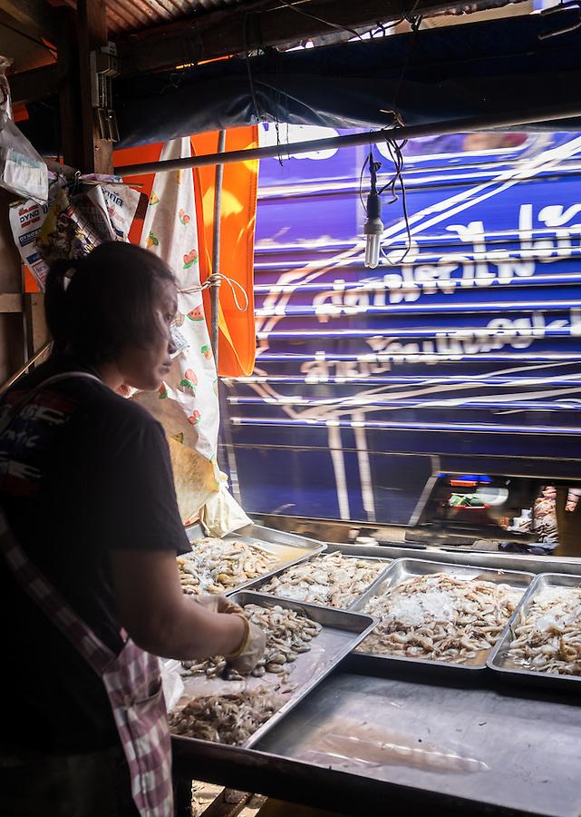 MAE KLONG - TAHILAND - CIRCA SEPTEMBER 2014: Merchant in the stalls of the Maeklong Railway Market
