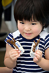 Ai Nakahodo, 3, a volunteer participating in the Team Tyura Sango coral reef restoration project, shows off her piece of coral to which is attached a ceramic name tag that will be placed into coral nurturing tanks before being bolted to the sea bed in the nearby bay in Onna Village, Okinawa Prefecture, Japan, on June 23, 2012.  Coral seedlings are put on small plates made of coral-like components, then fixed in place by wire and given a registration  number. They are raised at an aquafarm for several months before being bolted to the sea floor.Photographer: Robert Gilhooly