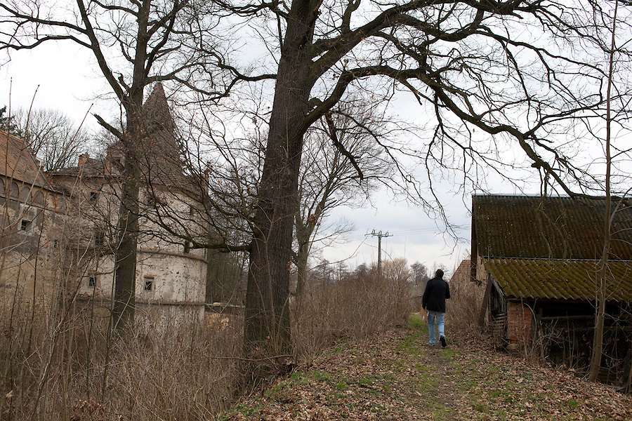 A man walking in the countryside of Červené Řečice, a rural village in southern Bohemia with a chateau ruin run by the Catholic Church, Czech Republic, Europe
