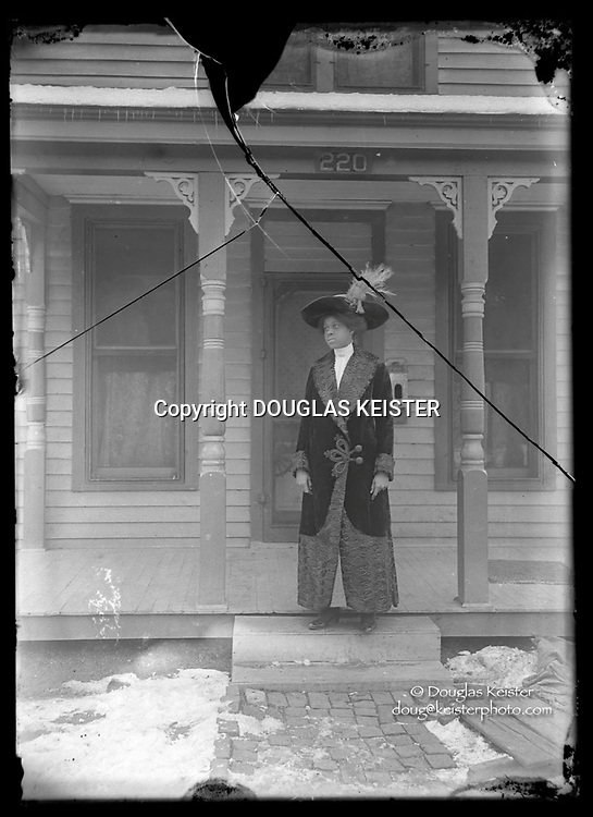 This woman MAY BE Vashti Agnes Knight (Mosby after marriage) (1891-1981) on the porch of her home at 220 South 20th Street circa 1910-1911.<br /> <br /> <br /> Photographs taken on black and white glass negatives by African American photographer(s) John Johnson and Earl McWilliams from 1910 to 1925 in Lincoln, Nebraska. Douglas Keister has 280 5x7 glass negatives taken by these photographers. Larger scans available on request.