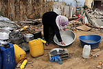 Palestinian woman washes the pot outside their destroyed house, on a winter cold day, in Khan Youns southern in Gaza city January 20, 2020. Photo by Ashraf Amra