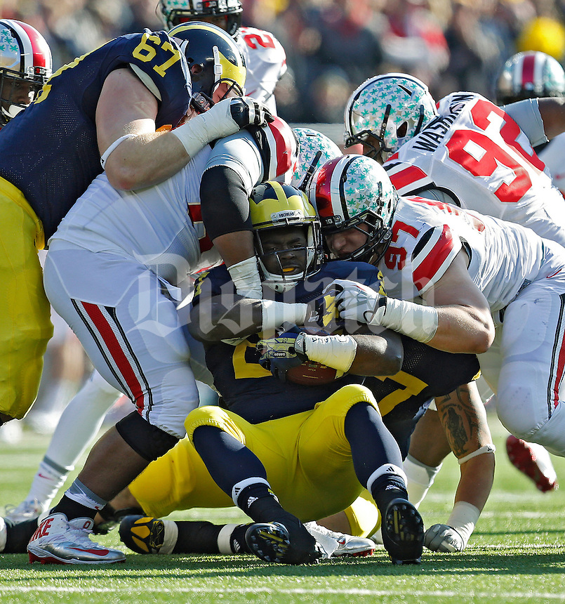 Ohio State Buckeyes defensive lineman Michael Bennett (63) and Ohio State Buckeyes defensive lineman Joey Bosa (97) stop Michigan Wolverines running back Derrick Green (27) in the 2nd quarter of their college football game at Michigan Stadium in Ann Arbor, Michigan on November 30, 2013.  (Dispatch photo by Kyle Robertson)