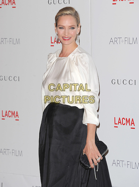 Uma Thurman.The Inaugural Art and Film Gala held at LACMA in Los Angeles, California, USA..November 5th, 2011   .half length black skirt side clutch bag white dangling diamond earrings.CAP/RKE/DVS.©DVS/RockinExposures/Capital Pictures.