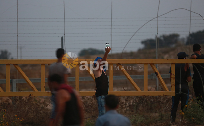"""Palestinian protestors gather after tearing down a section of a border fence between Israel and the Gaza Strip during clashes with Israeli security forces on October 12, 2015, east of Bureij in central Gaza. Palestinian foreign minister Riad al-Malki accused Israel of seeking to spark """"a third intifada"""", as violence again flared in Jerusalem, the West Bank and the Gaza Strip. Photo by Yasser Qudih"""