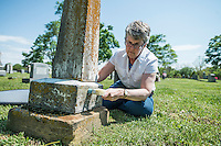NWA Democrat-Gazette/ANTHONY REYES &bull; @NWATONYR<br /> Abby Burnett, author, cleans some of the dirt of grime off a tombstone Tuesday, April 21, 2015 at Bluff Cemetery in Springdale.
