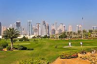 Dubai.  Skyline of Emirates Lakes Towers and Dubai Marina  overlooks the Montgomerie Golf Course at Emirates Hills.  Villa developments..