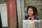 An indigenous girl smiles as she looks through a hole in a fence in the Nacoes Indigenas neighborhood in Manaus, Brazil. The neighborhood is home to members of more than a dozen indigenous groups, many of whose members have migrated to the city in recent years from their homes in the Amazon forest.