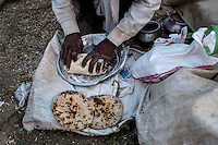 A man making Indian bread (roti) at Pushkar fair ground. Rajasthan, India.