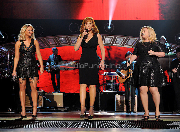 NASHVILLE, TN - DECEMBER 15: Miranda Lambert, Reba McEntire, and Kelly Clarkson perform onstage on the 2014 American Country Countdown Awards on FOX at the Music City Center on December 15, 2014 in Nashville, Tennessee. (Photo byFMPG/MediaPunch)