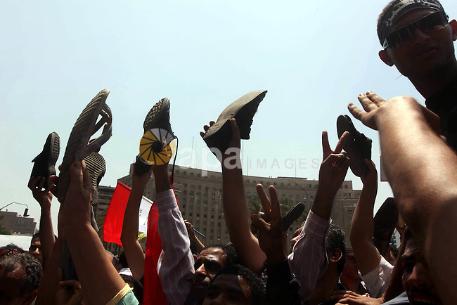 Egyptian protesters hold shoes and shout slogans against the presidential candidate Ahmed Shafik, during a protest in Tahrir Square, Cairo, Egypt, 01 June 2012. Media reports state that hundreds of Egyptians held a demonstration to protest against Egyptian presidential candidate Ahmed Shafik, who was appointed premier in Mubaraks final days in power. The runoff is scheduled for 16-17 June, while the winner will be announced on 21 June. Photo by Ashraf Amra