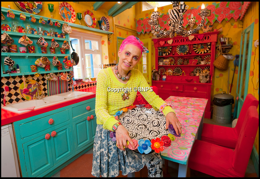 BNPS.co.uk (01202 558833)<br /> Pic: PhilYeomans/BNPS<br /> <br /> Artist Mary Rose Young in the kitchen.<br /> <br /> Britain's wackiest property has come on the market...And the estate agents mantra of paint everything magnolia has definately not been applied.<br /> <br /> It may look like an idyllic cottage in the Forest of Dean from the outside but ceramic artist Mary Rose Young's unique taste has transformed the interior into what looks like something from Alice in Wonderland.<br /> <br /> The three-bedroomed house is decorated from head to toe in crazy colours, clashing patterns, and enormous murals,<br /> each room is covered in the garish designs, including the bathroom, where even the sink and toilet have been adorned in bright tiles.<br /> <br /> Estate agents Bidmead Cook now have the tricky task of showing prospective punters round the £500,000 property.