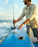 USA, Florida, mid adult man getting ready to reel in a fish, Destin