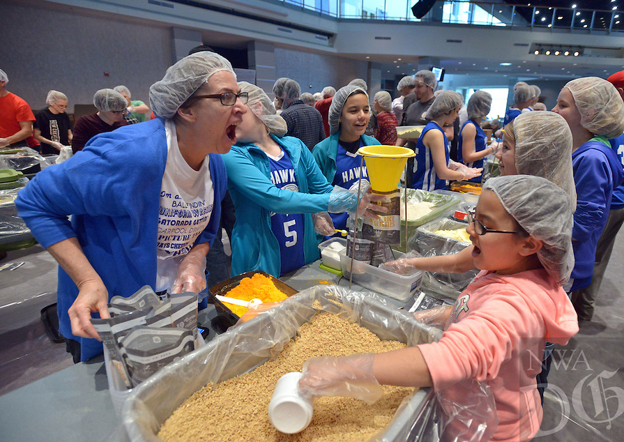 NWA Democrat-Gazette/BEN GOFF -- 03/13/15 Kelly Ribeiro (left) shows Chelsey Maya, 9, and members of her daughter's middle school girls' basketball team from Ozark Adventist Academy in Gentry how to call for a 'runner' to take their full trays of packed meals to be sealed while volunteering during The Pack Shack's NWA vs Hunger Feed the Funnel Party at Cross Church in Rogers on Friday Mar. 13, 2015. Over 1,300 people are scheduled to participate in The Pack Shack event in eight 1-2 hour shifts over Thursday, Friday and Saturday, packing dry goods for over 50,000 meals that will be distributed to area food banks.