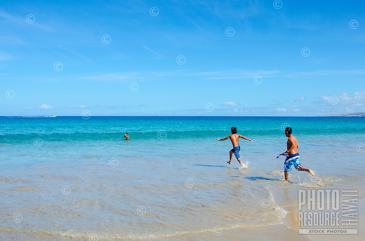 Two teenage boys running into the ocean at Hapuna Beach, along the Big Island's Kohala Coast. This white sand beach has been rated one of the best beaches in the world time and time again.