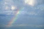 Rainbow below puffy white cumulonimbus storm clouds in blue sky.